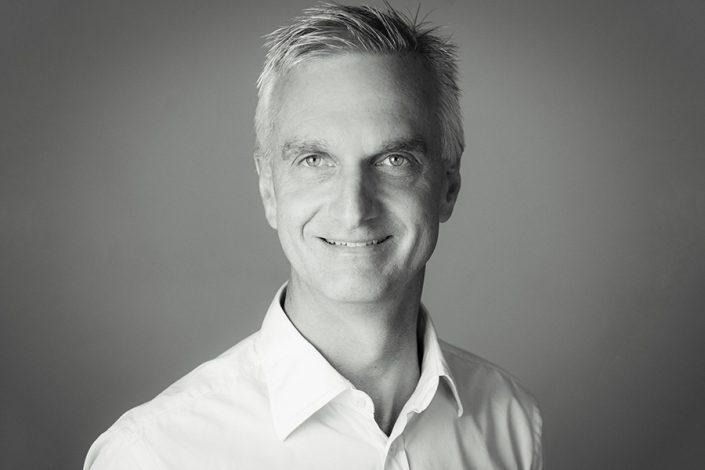 Black & White headshot of a man on grey background