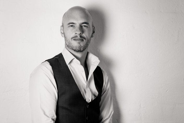 Headshot photo of a man on white textured background