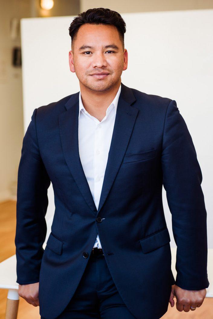 Informal Business Portrait. Man standing in navy suit.
