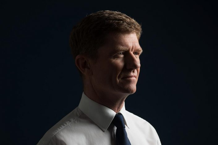 Photo of a businessman against a navy background in a shirt and tie