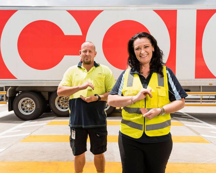 Photo of two people in front of a delivery truck